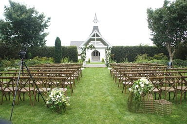 oak valley arch with wooden cross back chairs and white flowers