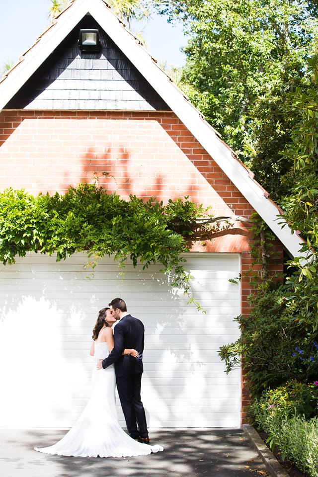 red brick garage with wisteria and bride and groom