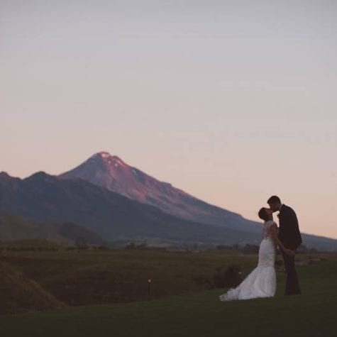 bride and groom kissing under the mountain