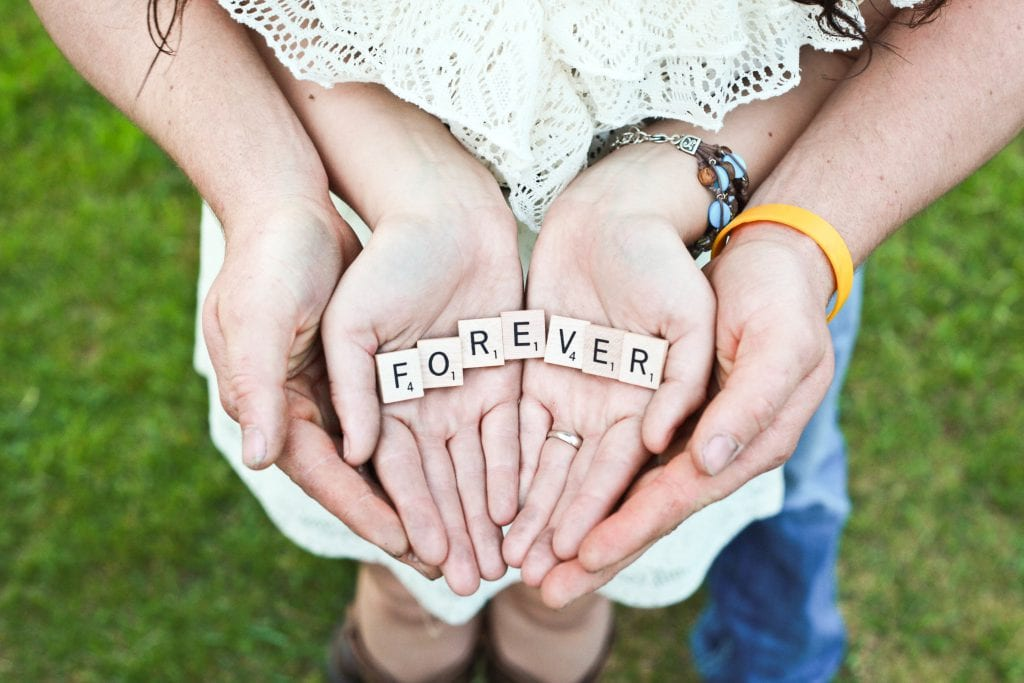 bride and groom hands holding lettters in forever