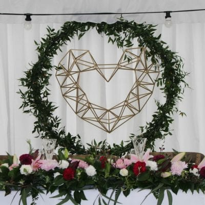gold geometric heart backdrop with greenery